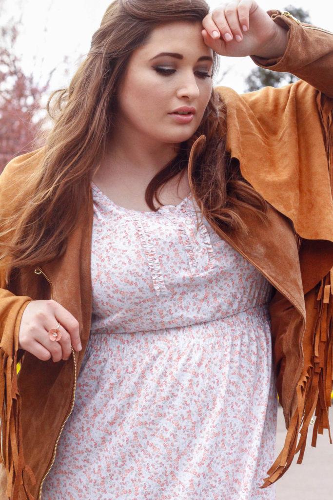 Plus Size Woman posiert in einer Congnac Lederjacke mit einem Blumenkleid und Boots