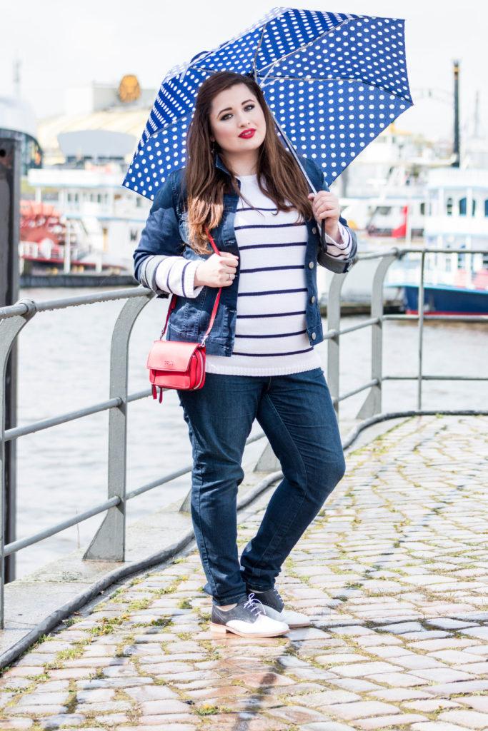 Kurviges braunhaariges Mädchen mit Regenschirm am Hamburger Hafen