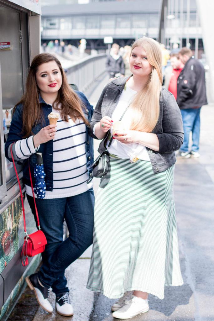 Zwei kurvige Mädchen, Eis essend und lachend in Hamburg