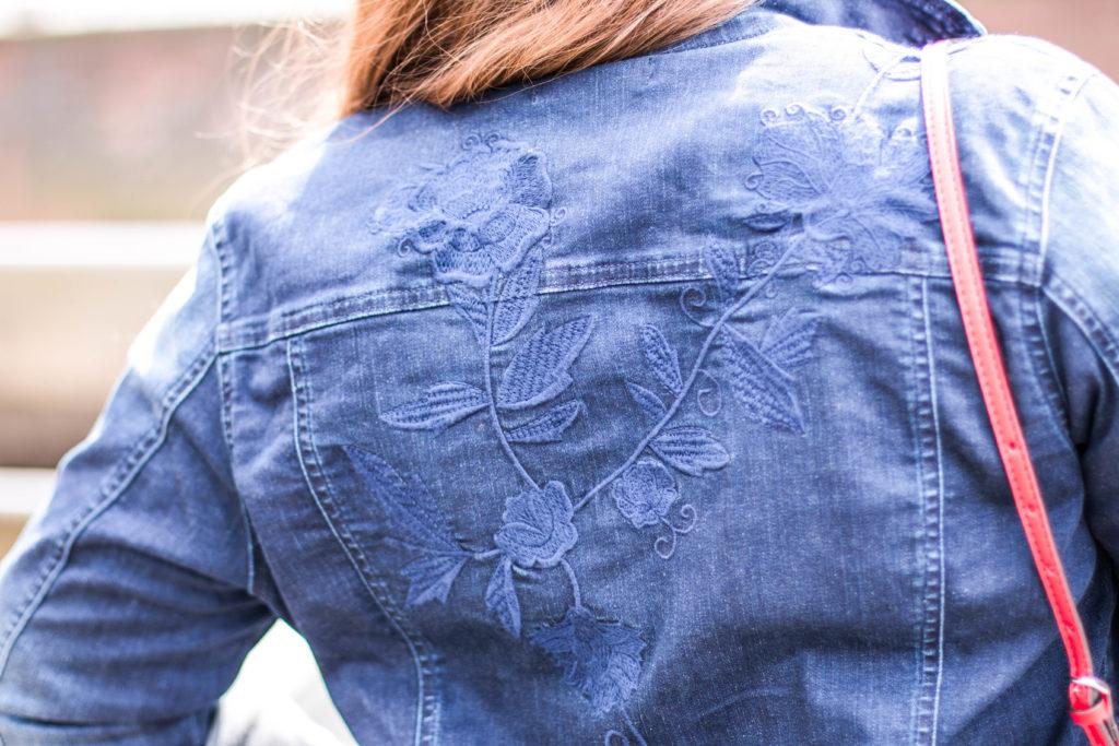 Blaue Jeansjacke mit Applikation von hinten im Anschnitt