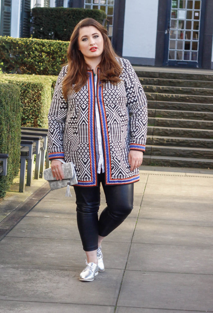 Plus Size Fashion Ethno Look. Curvy Woman with Ethno Coat, Leather Leggings and Silver laced Shoe.