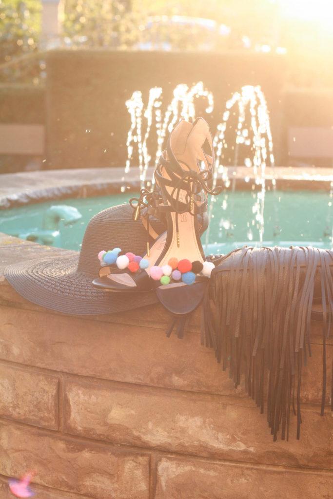 Schuhe, Tasche, Hut, schwarz am Brunnen.