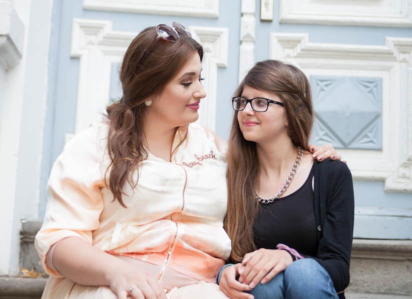 Große kräftige Schwester und kleine zarte Schwester sitzen nebeneinander und sprechen