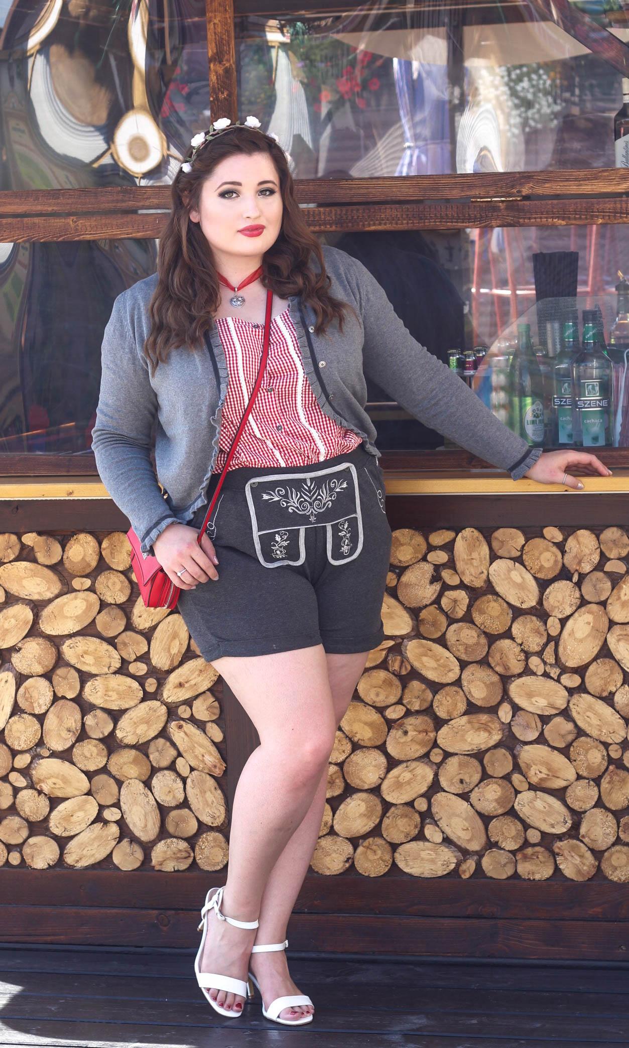 Junge kurvige Frau vor einer Holzhütte im Oktoberfest Outfit. Plus Size Lederhosen Look.