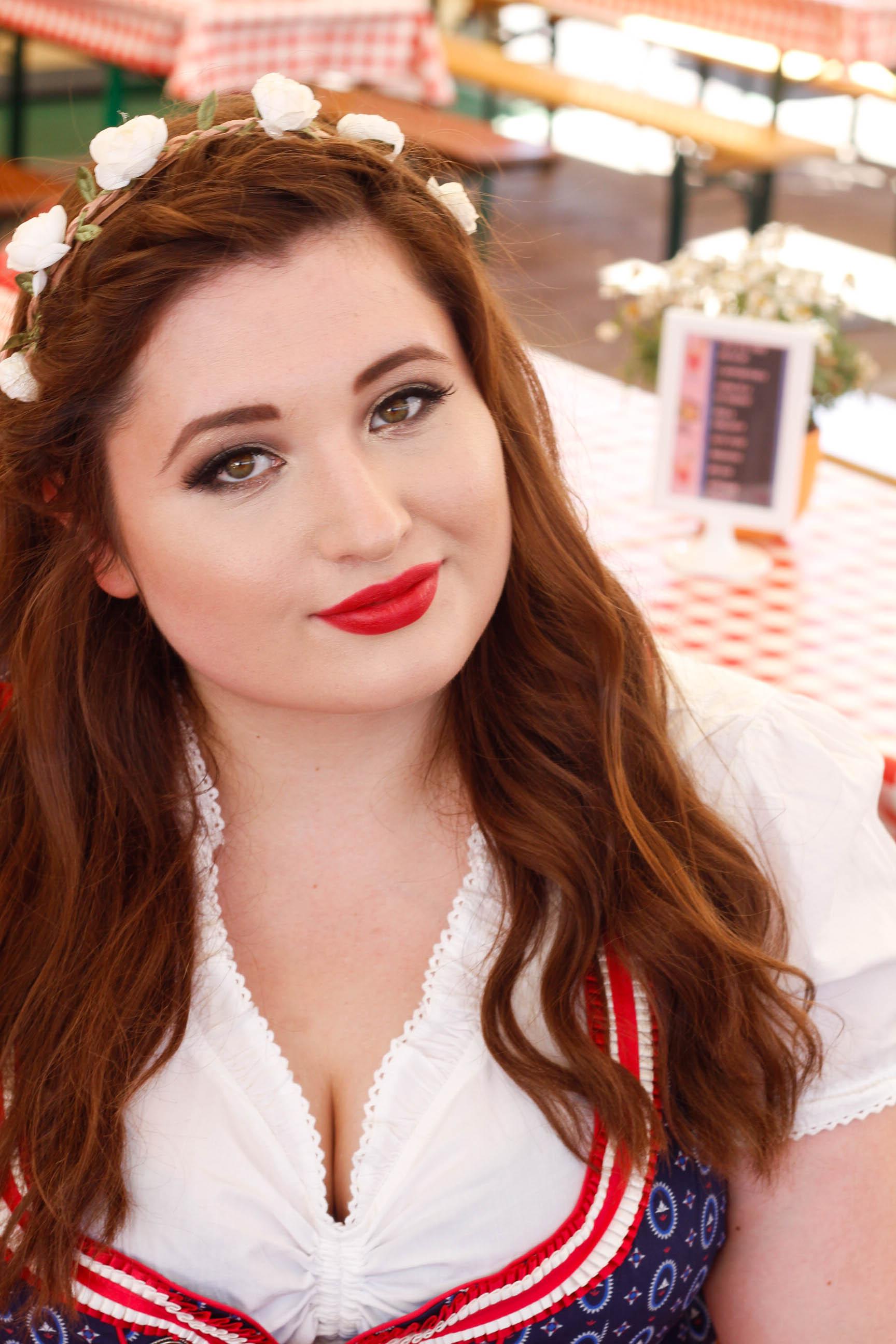 Junge kurvige Frau vor einer Holzhütte im Oktoberfest Outfit. Plus Size Look. Flechtfrisur mit Rosen.