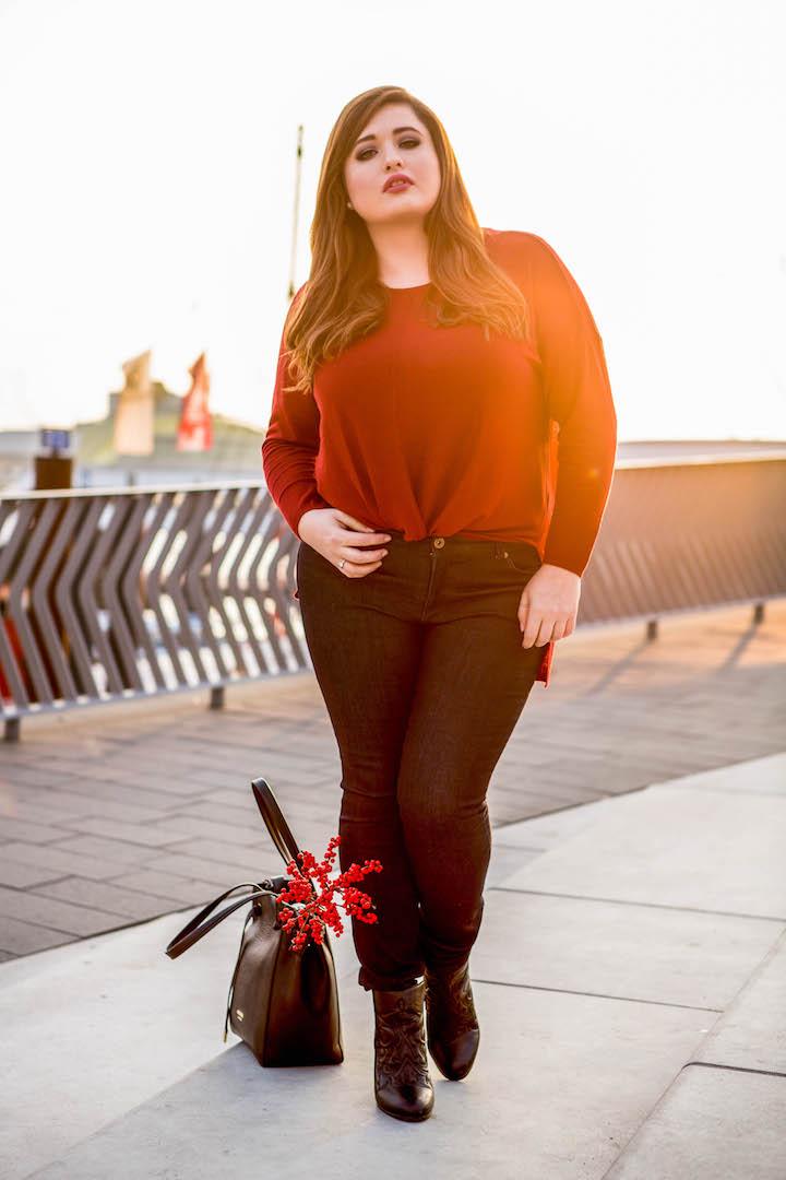 SchönWild Plus Size Model mit rotem Feinstrick Shirt, dunkelblauer Jeans und schwarzen Stiefeletten in Hamburg im Herbst